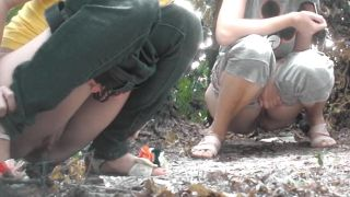 Two brunettes caught pissing together