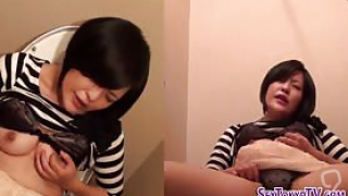 Asian teen rubbing her pussy while sitting on the toilet
